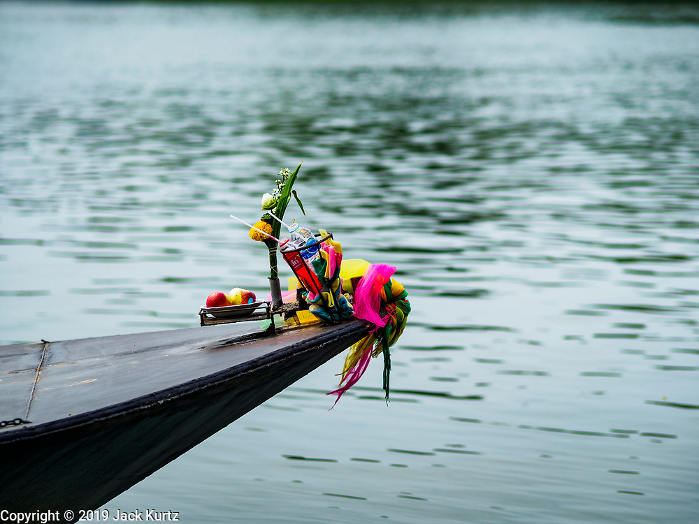 "09 JANUARY 2019 - KANCHANABURI, THAILAND:  An offering on the bow of a small ferry that takes people acrss the River Kwai. The ferry goes across the River Kwai downriver from downtown Kanchanaburi, the site of the famous ""Bridge on the River Kwai."" Small ferries like this, once common on Thai river crossings, are disappearing because Thailand has dramatically improved its infrastructure since this ferry started operating about 50 years ago. The ferry operator said his grandfather started the ferry, with a small raft he would pole across the river, in the late 1960s. Now his family has a metal boat with an inboard engine. There are large vehicle bridges across the river about 5 miles north and south of this ferry crossing, but for people in rural communities on the west side of the river the ferry is still the most convenient way to cross the river.     PHOTO BY JACK KURTZ"