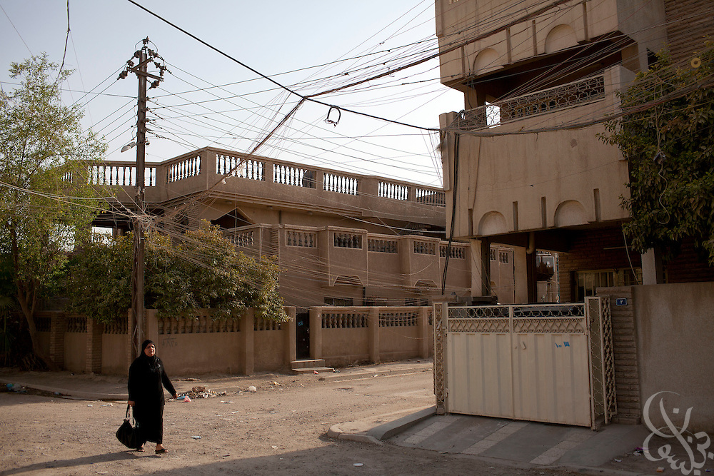 An Iraqi woman walks underneath a tangle of home-rigged electrical wires on a Baghdad street August 23, 2010.  After seven years of conflict, Iraqis still rely heavily on the use of neighborhood or private generators as the iraqi civil electrical grid has struggled to keep pace with demand despite numerous projects to rebuild Iraq's infrastructure and electrical capacity.  .