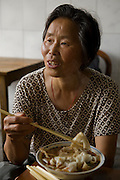 Widowed farmer Lan Guihua enjoys lunch at a small restaurant in a market town near Ganjiagou Village, Sichuan Province, China. (Lan Guihua is featured in the book What I Eat: Around the World in 80 Diets.)  MODEL RELEASED.