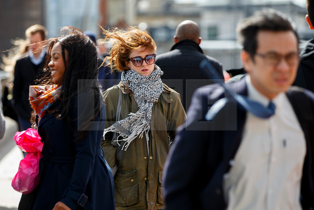 © Licensed to London News Pictures. 31/03/2015. LONDON, UK. Commuters walking against strong wind on London Bridge as gale force winds reach 65mph in London on Tuesday, 31 March 2015. Photo credit : Tolga Akmen/LNP