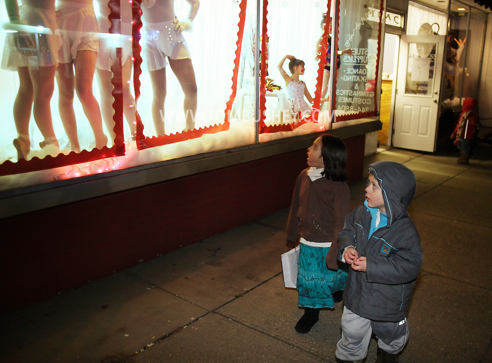Pine Bush, New York - Two children walking on the sidewalk look at dancers from the Mitchell Performing Arts Center posing in a storefront window during the Pine Bush Festival of Lights on Dec. 4, 2010.