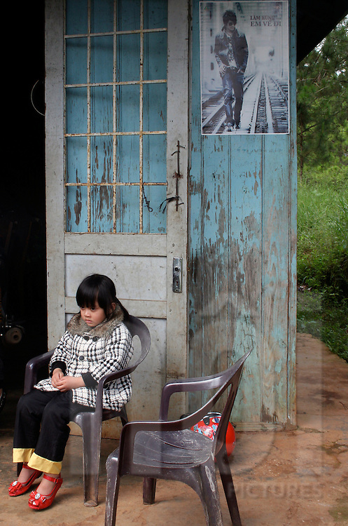 Portrait of a little girl sitting on a plastic chair. Oct 2010.Dalat, Vietnam