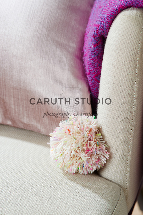 Pom-pom decorating corner of accent pillow