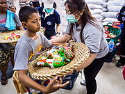18 SEPTEMBER 2017 - BANGKOK, THAILAND: A volunteer helps a boy carry a basket of food at Poh Teck Tung in Bangkok. The Ghost Festival, also known as the Hungry Ghost Festival, Zhongyuan Festival or Yulan Festival is a traditional Buddhist and Taoist festival held in Asian countries. According to the Chinese calendar (a lunisolar calendar), the Ghost Festival is on the 15th night of the seventh month. In Chinese culture, the fifteenth day of the seventh month in the lunar calendar is called Ghost Day and the seventh month in general is regarded as the Ghost Month, in which ghosts and spirits, including those of the deceased ancestors, come out from the lower realm. Distinct from both the Qingming Festival (in spring) and Double Ninth Festival (in autumn) in which living descendants pay homage to their deceased ancestors, during Ghost Festival, the deceased are believed to visit the living.     PHOTO BY JACK KURTZ