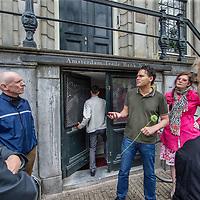 Nederland, Amsterdam, 18 mei 2017.<br /> fietstocht kamerplant tour. Een initiatief van kunstenares Tinkebell en financieel journalist Arno Wellens om de brievenbusfirma&rsquo;s in Nederland in het daglicht te zetten.<br /> De fietstocht voor ge&iuml;nteresseerden start tegenover de Nederlandsche Bank en gaat uiteindelijk via de stad naar de Zuidas. Ondertussen wordt er door brievenbussen gegluurd en vertelt Arno Wellens alles over de brievenbusfirma&rsquo;s met hun kamerplantkantoortjes in Amsterdam. 1 kantoor zou liefst 10.000 van deze firma&rsquo;s huisvesten.<br /> Op de foto: Arno Wellens geeft uitleg voor Amsterdam Kredietbank aan de Herengracht terwijl een medewerker naar binnen glipt.<br /> <br /> <br /> Foto: Jean-Pierre Jans