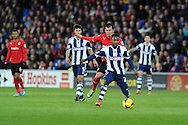 West Brom's Stephane Sessegnon © breaks away from Cardiff's Gary Medel. Barclays Premier league, Cardiff city v West Bromwich Albion at the Cardiff city Stadium in Cardiff, South Wales on Saturday 14th Dec 2013. pic by Andrew Orchard, Andrew Orchard sports photography.