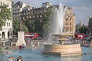 Fountain, passing double decker buses, Trafalgar Square, London, England