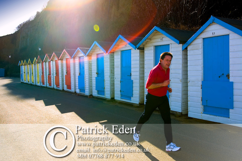 Jogger, Runner, Coloured Beach Huts, Shanklin, Isle of Wight, England, UK, Photographs of the Isle of Wight by photographer Patrick Eden photography photograph canvas canvases