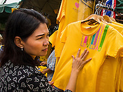 28 NOVEMBER 2014 - BANGKOK, THAILAND:  A woman in Bangkok buys a tee shirt before the King's Birthday in Thailand. Bhumibol Adulyadej, the King of Thailand, was born on December 5, 1927, in Cambridge, Massachusetts. The family was in the United States because his father, Prince Mahidol, was studying Public Health at Harvard University. He has reigned since 1946 and is the world's currently reigning longest serving monarch and the longest serving monarch in Thai history. Bhumibol, who is in poor health, is revered by the Thai people. His birthday is a national holiday and is also celebrated as Father's Day. He is currently hospitalized in Siriraj Hospital, recovering from a series of health setbacks. Thousands of people come to the hospital every day to sign get well cards for the King. People wear yellow at events associated with the King because he was born on a Monday, and yellow is Monday's color in Thai culture. It's also the color of the monarchy.      PHOTO BY JACK KURTZ