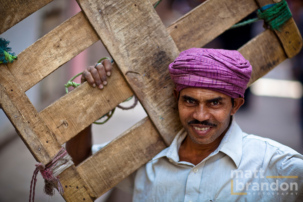 A Muslim man carries a wooden flat down the street in Old Delhi.