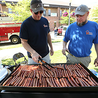 Jason Miller and Richard Walls, with Hometown Healthcare cook up hotdogs for the LIFE and Our Artworks cookout and Resource Fair Tuesday at Fairpark in Tupelo. Hometown Healthcare provided food, drinks and the cooking. The goal for the event is to bring the community together through awareness, knowledge, and networking.