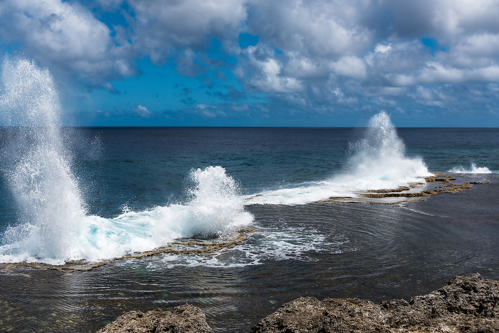 Water shoots to the sky from blowholes on the coastline of Alofa as the tide rolls in.