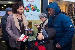 Oxford Street, London, December 5th 2014. Actor and Comdeian turned political activist Russel Brand visits several big brands'  stores including Boots, Apple and Vodafone in London accusing them of dodging tax whilst those most in need of benefits are facing cuts and increased hardship. A leaflet being distributed by him claims £14 billion is lost every year, through tax avoidance and loopholes exploited by big business. PICTURED: Russel Brand, en route to Vodafone's Oxford Street store, speaks with a disabled person about benefits cuts.