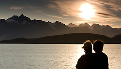 Unidentified passengers on the Alaska Marine Highway System ferry m/v Malaspina enjoy the scenery of the Lynn Canal as the sun sets behind the Chilkat Range near Haines, Alaska.