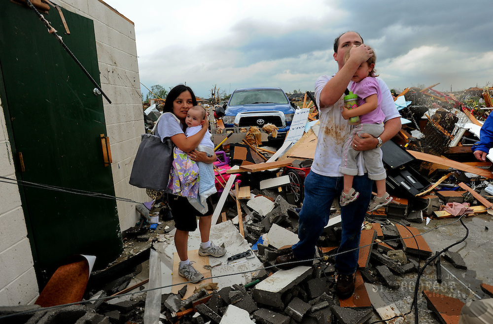 Photo by Gary Cosby Jr.  Homes in the McCulley Mill Rd. area are completely destroyed following a large tornado that cut a path through Lawrence, Morgan and Limestone Counties.  Kevin Harrison and his wife Sarabeth hold their children, Mason and Sophie as they emerge from a safe room, the only thing that survived of their house.