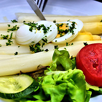 White Asparagus on Plate in Luxembourg City, Luxembourg<br /> My wife loves white asparagus, so during spargel season in Western Europe, she can hardly wait to enjoy a dinner of the spears garnished with an egg, a lettuce sprig and a slice of tomato and cucumber.  This asparagus is the same as the green variety but it is denied sunlight which prevents photosynthesis.  Some sandy soils of Germany are big producers and they host spargel tourist routes, festivals and even have a spargel queen.