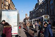 In Amsterdam steken toeristen op het Damrak het fietspad over terwijl er een fietser aankomt. Twee toeristen proberen met de kaart en plattegrond te orienteren waar ze zijn. Een tram staat bij de tramhalte. Onlangs zijn de rijbanen op het Damrak aangepast met een duidelijkere scheiding tussen fietsers, trambaan en autoverkeer. <br /> <br /> In Amsterdam tourists on the Damrak cross the bike path while there comes a cyclist. Two tourists try to orient the map and plan where they are. A tram is at the tram stop. Recently, the lanes on the Damrak are adjusted with a clearer separation between cyclists, tram and car traffic.