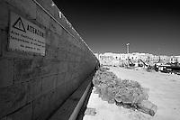 Nasse depositate sul molo del porto di Gallipoli (LE), il cartello sul muro avverte che questa zona è proprio adibita al deposito delle attrezzature da pesca.