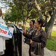 NORTH MIANI, FLORIDA, NOVEMBER 8, 2016<br /> Move On volunteers Lorna Shuford and her mother Delma Rodriguez  hand out signs to resident Andrew Richards as they go knocking on doors of homes of voters in the North Miami area as they canvass for democratic votes.<br /> (Photo by Angel Valentin/Freelance)