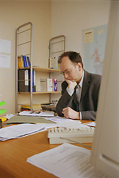 Man working at desk in translation agency office; analysing sales figures,