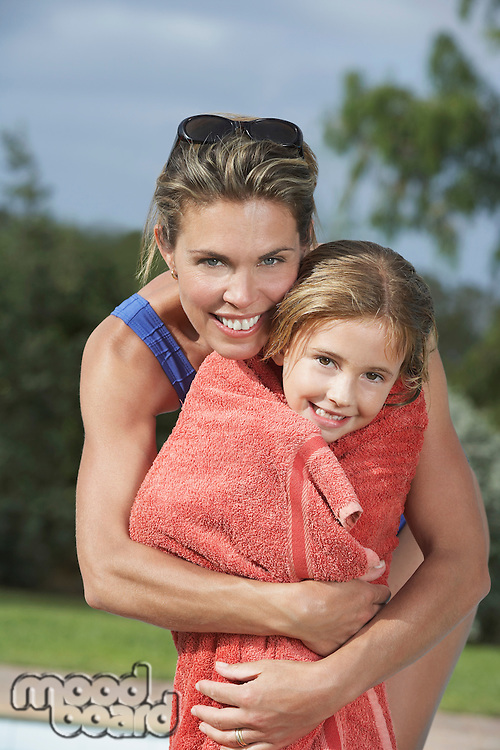 Portrait of mother embracing daughter (5-6) wrapped in towel