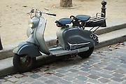 Classic old grey two seated motor scooter in the streets of Paris, France.Klassischer alter 2-sitziger Motorroller in den Strassen von Paris, Frankreich