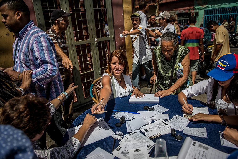 CARACAS, VENEZUELA - JULY 16, 2017: Today, at over 2,000 polling locations, Venezuelans participated in a symbolic vote, called by the political opposition to the Socialist government. Ballots had three questions: ONE - Do you refuse the government's plans for a new constituent assembly, without prior approval from the people, TWO - Do you demand that government employees obey and defend the 1999 Constitution and respect the decisions of the National Assembly, and THREE - Do you approve that powers should be established by the Constitution, and that we should have free and transparent elections? The opposition held this vote, as a massive act of civil disobedience to show that the people disapprove of the government. For over 3 months, anti-government protests have raged across Venezuela.  PHOTO: Meridith Kohut