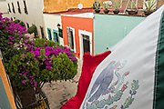 The Mexican flag flies over a colorful alley in the old colonial section of Santiago de Queretaro, Queretaro State, Mexico.