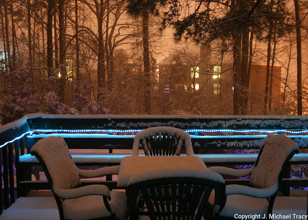 Deck chairs covered with snow during a rare southern snowstorm. Blue rope lights surround the deck glowing with a beautiful blue light.
