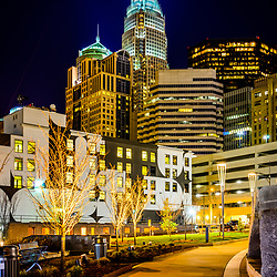 Downtown Charlotte city at night with Romare Bearden Park sidewalk. Charlotte, North Carolina is a major city in the Eastern United States of America. Includes Bank of America Corporate Center, Bank of America Plaza, and 121 West Trade buildings.