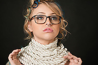 Close-up of beautiful young woman wearing retro glasses with rope around neck looking away over colored background