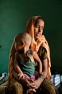 "Shashi Devi (aged 28) sits in her house in the village of Shahpurjat, Ghaziabad, Uttar Pradesh, India. While Shashi had a tubectomy done after having 2 sons, Monika, her brother-in-law's wife, is still trying for a son after having 2 daughters. Shashi did the operation because she wanted to ""give her 2 children the best and inflation will make things difficult"", and she believes that a ""small family = happy family"". She has been pushing Monika to get her husband to do an NSV so that Monika's life is not endangered since her previous pregnancies have been complicated. Photo by Suzanne Lee / Panos London"