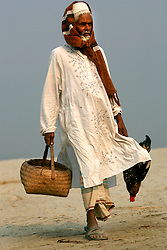 BANGLADESH SIRAJGANJ RADHUNIBARI 30JAN07 - Elderly Bangladeshi man dressed in traditional Muslim garb carries a basket and a chicken on the banks of a tributary to the Jamuna river, an area traditionally prone to flooding during the Monsoon season...jre/Photo by Jiri Rezac..© Jiri Rezac 2007..Contact: +44 (0) 7050 110 417.Mobile:  +44 (0) 7801 337 683.Office:  +44 (0) 20 8968 9635..Email:   jiri@jirirezac.com.Web:    www.jirirezac.com..© All images Jiri Rezac 2007 - All rights reserved.