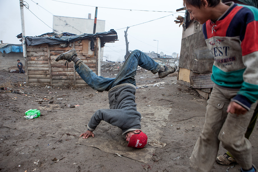 "Man showing his break dance skills in the middle of the Roma settlement located in ""Budulovskej Street"" in Moldava nad Bodvou, Eastern Slovakia about 30 km from Kosice."
