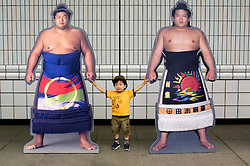 Young boy stands between two life size photographs of famous sumo wrestlers at tournament in Tokyo Japan