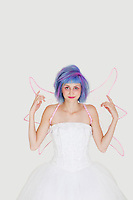 Portrait of happy young woman dressed as angel with dyed hair against gray background