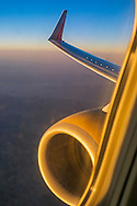 Looking out of jet airline window over engine and wing at sunset