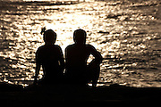 Couple silhouetted against the ocean