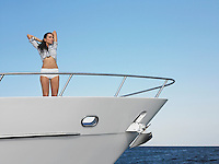Young woman standing in bow of yacht