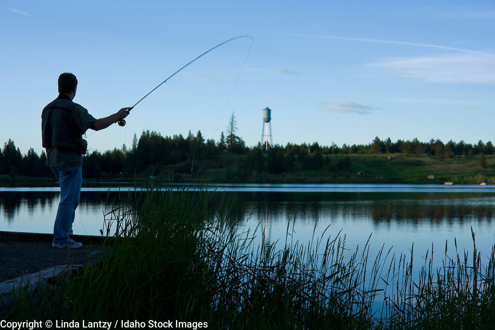 Silhouette of a man casting a fly rod from the shore at dusk. Winchester Lake, Winchester, Idaho, USA.