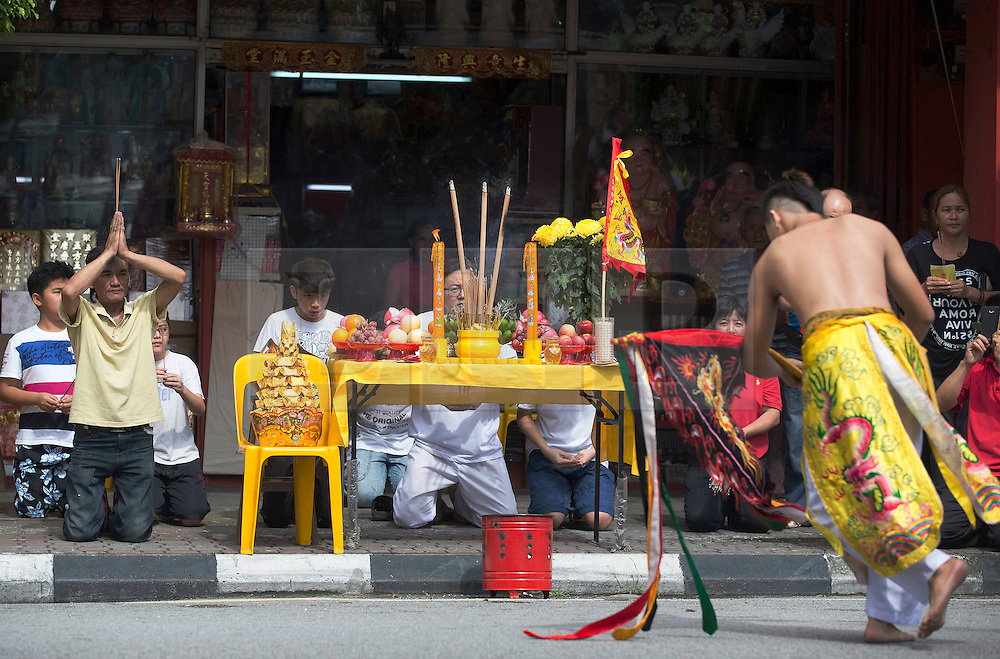 © Licensed to London News Pictures. 28/09/2014. Ipoh, Malaysia. Members of a shop pray with their offerings as devotees process with deities through the streets of central Ipoh, Malaysia on the 5th day of the Nine Emperor Gods Festival, Sunday, Sept. 28, 2014. The festival is a nine-day Taoist celebration to mark the birth of the Nine Emperor Gods from the first day to the ninth day of the ninth moon in Chinese Lunar Calender. The origin of the Nine Emperor Gods (stars of the Northern constellation) can be traced back to the Taoist worship of the Northern constellation during Qin and Han Dynasty and absorb this practice of worshipping the stars and began to deitify them as Gods. Photo credit : Sang Tan/LNP