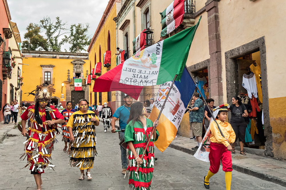 Costumed Aztec indians follow a statue of Saint Michael in a religious procession through the city at the start of the week long fiesta of the patron saint Saint Michael  September 21, 2017 in San Miguel de Allende, Mexico.