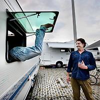 Nederland, Amsterdam , 1 oktober 2014.<br /> De rij caravans met mensen die een zelfbouwkavel willen kopen op het Zeeburgereiland wordt steeds groter.<br /> Sommige staan al een paar weken in de wachtrij totdat ze een kavel mogen kopen. Pas volgende week zaterdag gaan de kavels pas in de verkoop, maar wie weg gaat, verliest zijn plek in de rij.<br /> Een van de kampeerders staat er al een tijdje in zijn caravan: 'Ik ben hier behoorlijk vroeg gaan staan, want er is &eacute;&eacute;n kavel waar ik echt ge&iuml;ntresseerd in ben. Er hoeft er maar een eerder te zijn en dan ben je 'm kwijt.'<br /> De wachtende kopers vinden het best gezellig op het terrein: 'Je ontmoet een soort van je toekomstige buren als het zo doorgaat. Dat geeft een apart campinggevoel en we barbecuen samen.'<br /> Een probleempje, als je weggaat ben je je plek kwijt. 'Als je moet werken moet je zorgen dat er iemand anders op je plek zit. Ik had hier eerst helemaal geen zin in, maar het is toch wel een bizar avontuur.'<br /> Op de foto: 1 van de potentiele kavelkopers had zichzelf buitengesloten en klimt vervolgens weer via het raam van zijn gehuurde caravan naar binnen.<br /> Foto:Jean-Pierre Jans