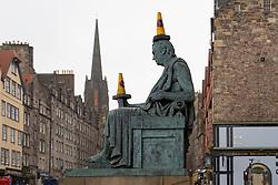 Edinburgh, Scotland, UK. 18 March 2020.Traffic cones placed on statue of David Hume on the Royal Mile in Edinburgh. Iain Masterton/Alamy Live News.