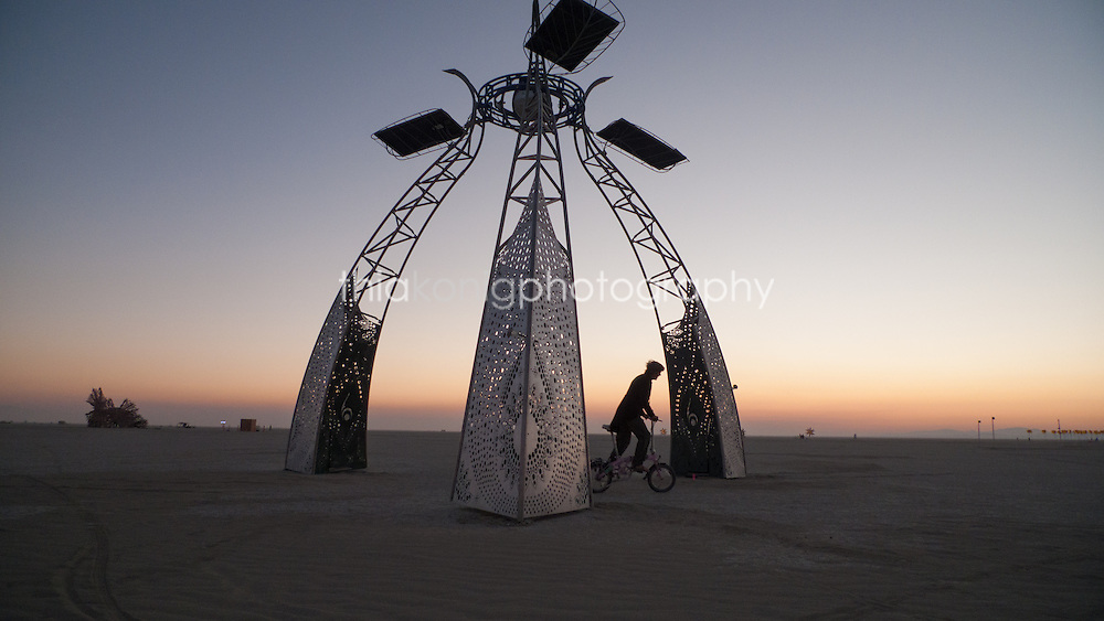 Man wearning coat and tails on a bicycle rides through a future looking art installation at dawn, Burning Man.
