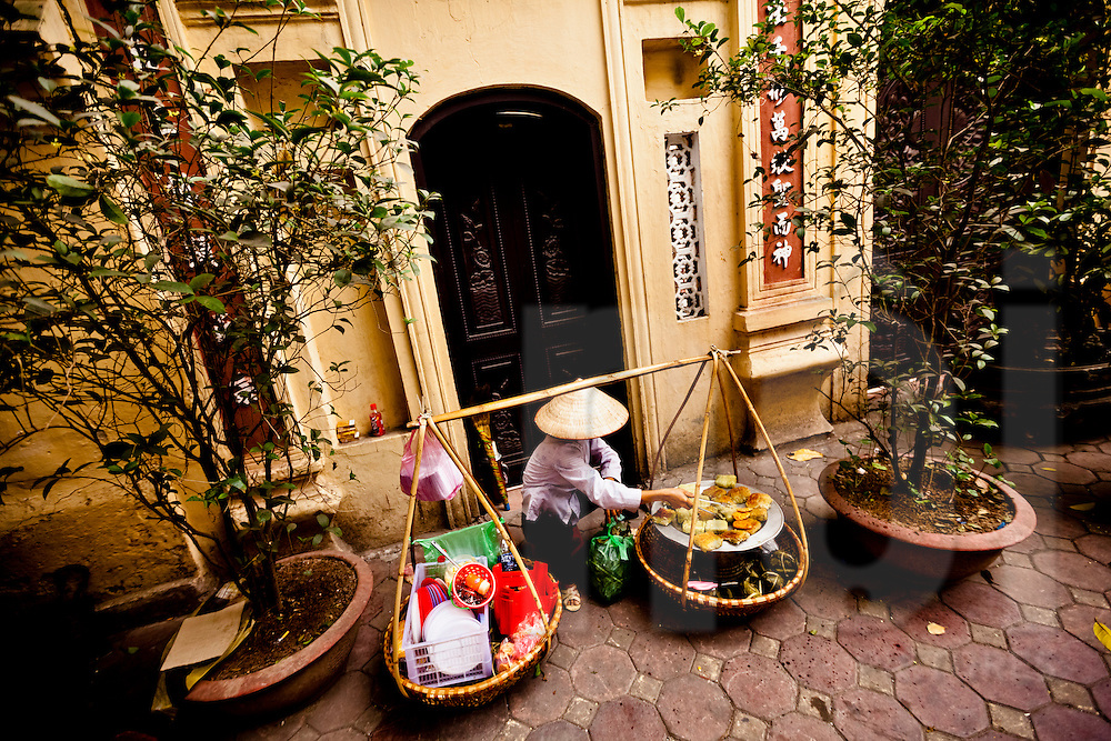 Vietnamese woman cooks rice cakes in front of a temple gate, Hanoi, Vietnam, Southeast Asia