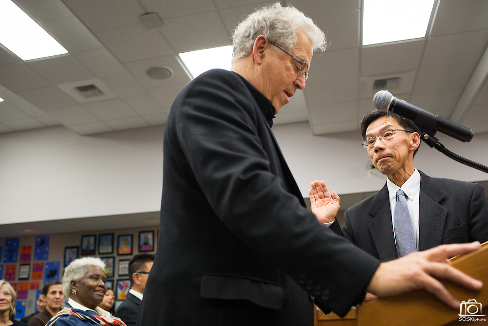 Returning Board member Danny Lau, right, is sworn into office by Joseph Weinstein during the Milpitas Unified School District Board of Education Administration of the Oath of Office ceremony at the Board of Education in Milpitas, California, on December 9, 2014. (Stan Olszewski/SOSKIphoto)