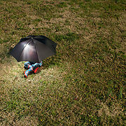 A 3-year-old Caucasian hides underneath a black umbrella out in a field. He is wearing a rain coat and boots that have red tractors on them.