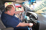 EAMC emergency room employee John Cowen tests out the radio in his new van Thursday.  Cowen's previous vehichle was unreliable, and the ER department joined together to purchase a new vehichle for him.  Photo by Elliot Knight