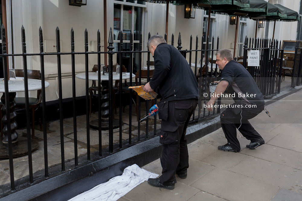 Two workmen paint black iron railings of a restaurant on Dean Street in the heart of Soho, on 5th March 2018, in London, England.